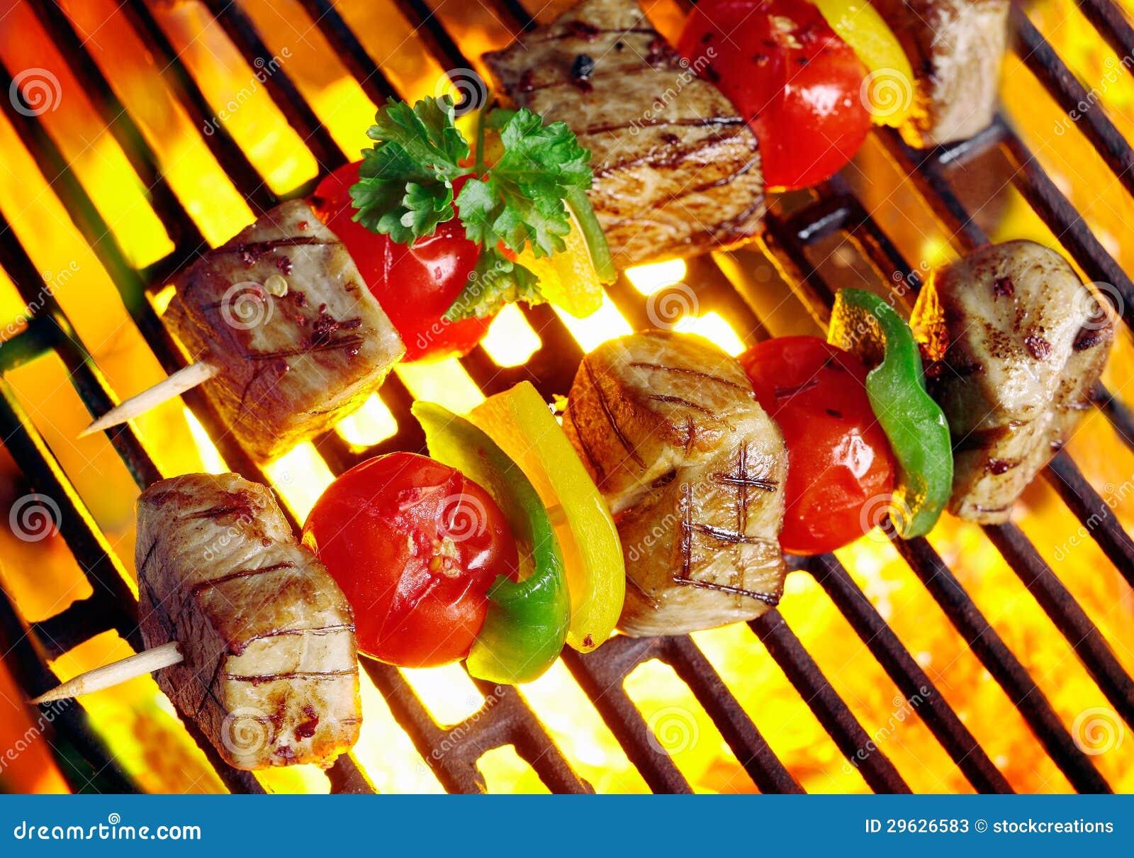 Kebabs da carne crepitantes sobre os carvões