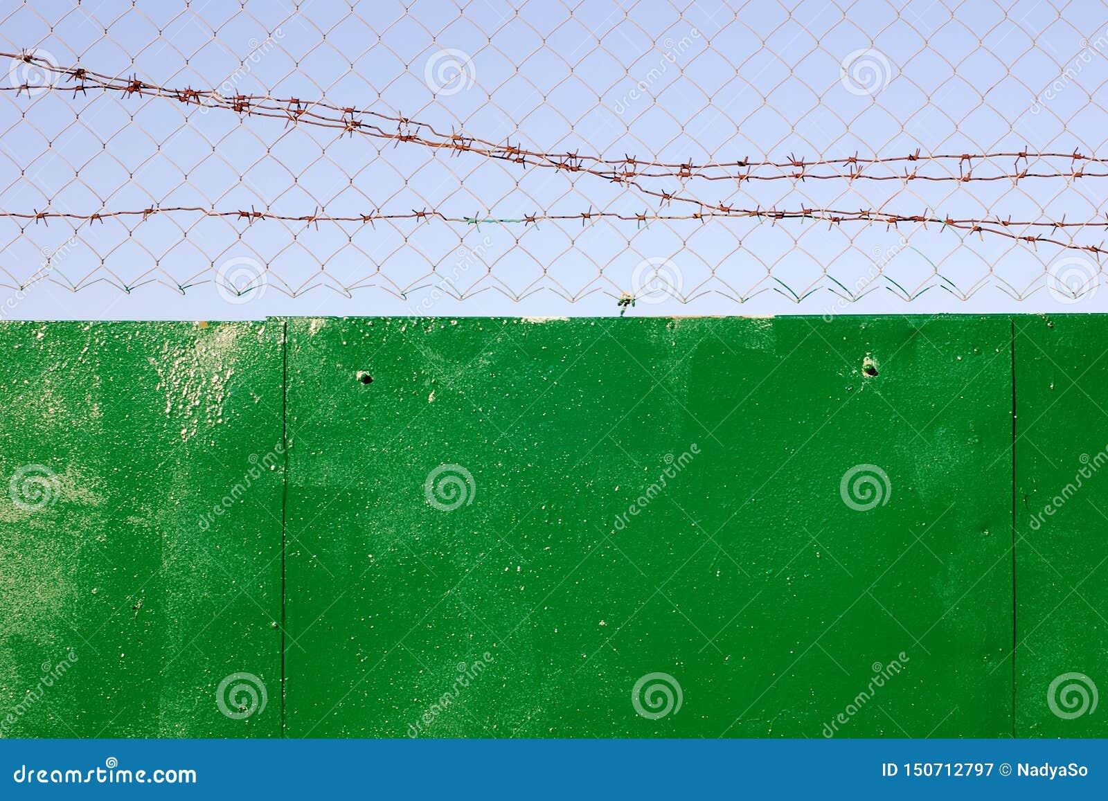 Kedja-sammanlänkning och taggtråd överst av det gröna staketet