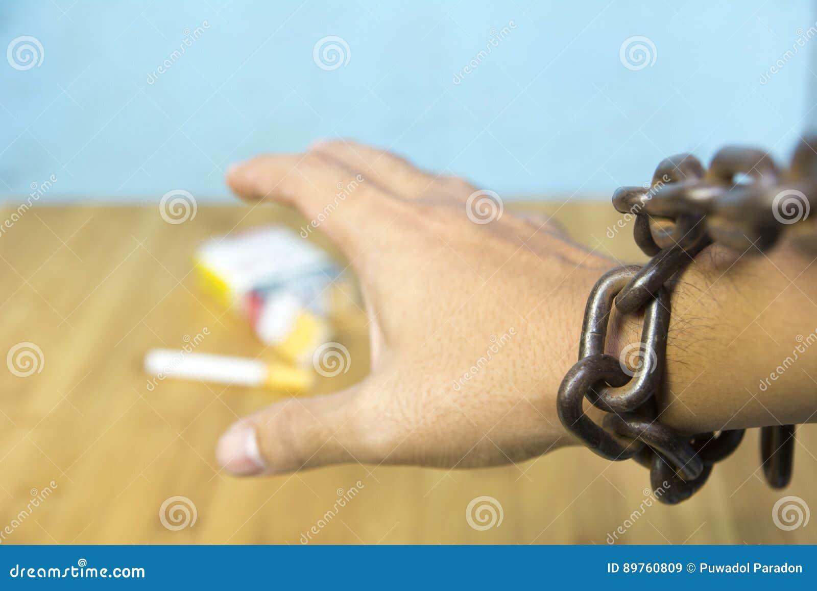 Kedjad fast mänsklig hand som försöker att fånga cigaretten på tabellen