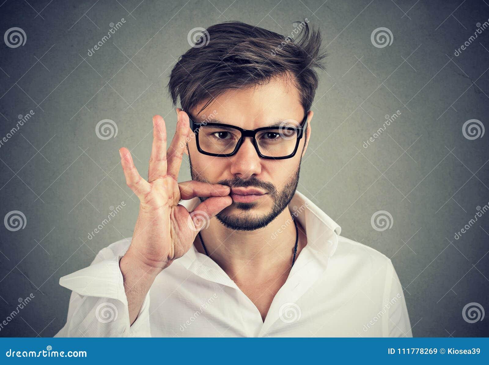 Keep a secret, man zipping his mouth shut. Quiet concept