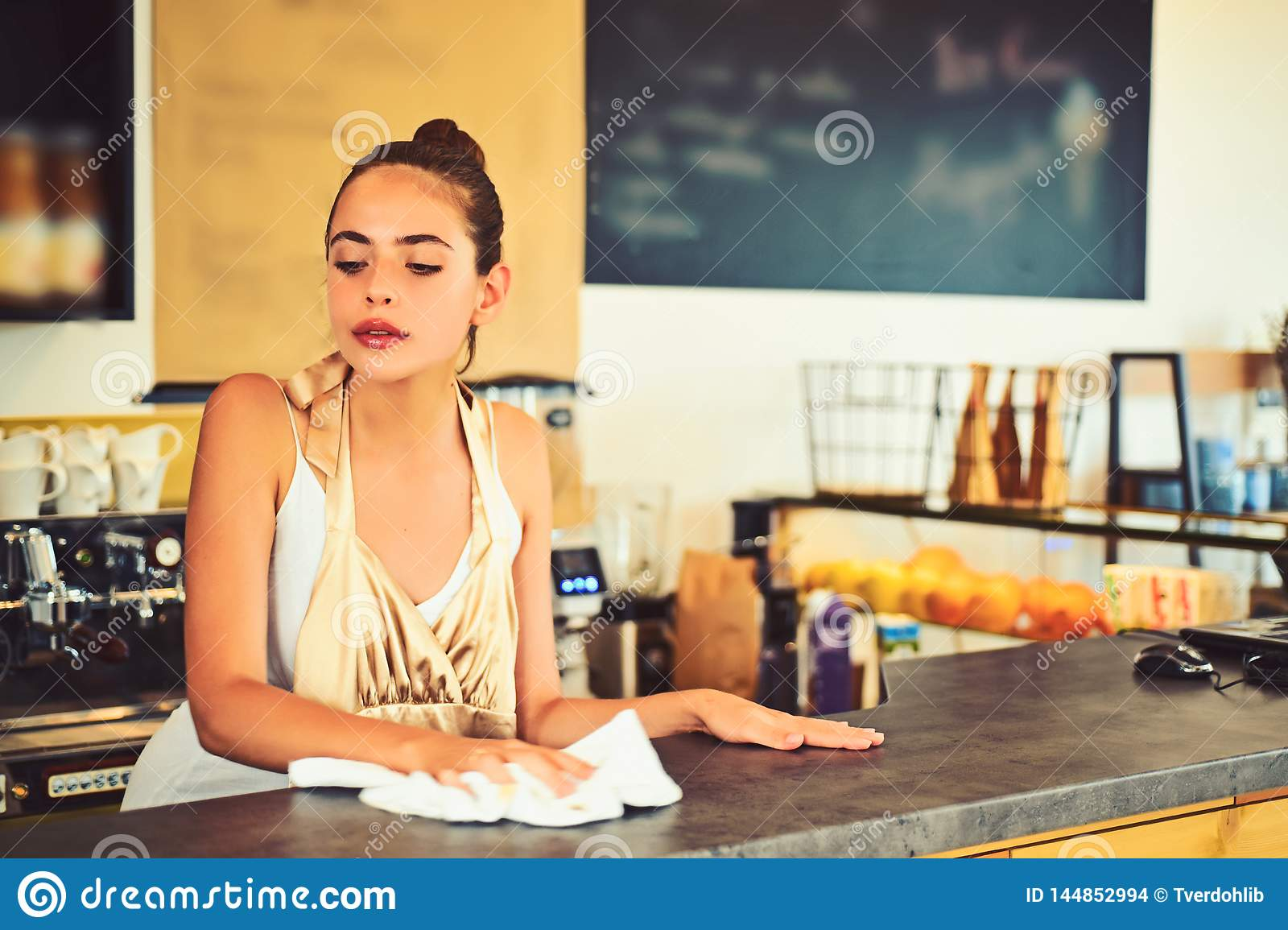 Keeping everything clean. Pretty woman stand behind cafe counter. Cute bartender or bar keeper. Barista clean counter