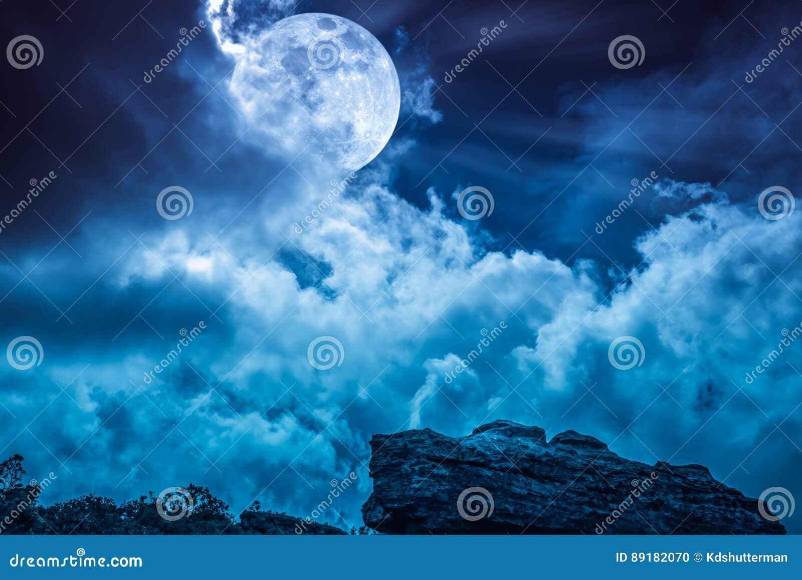 Kei tegen blauwe hemel met wolken en mooie volle maan bij