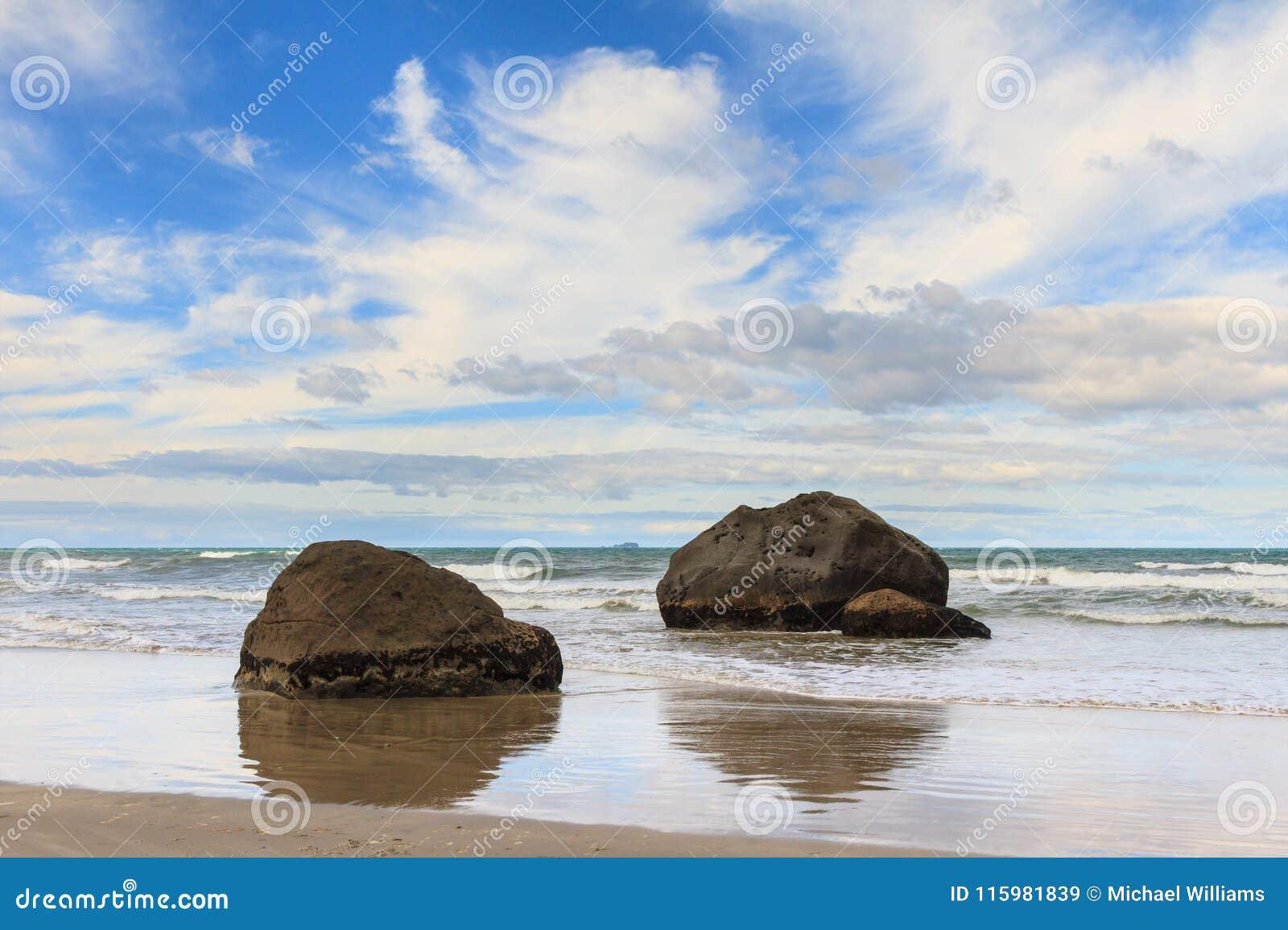 Keien in het glanzende zand van een strand worden weerspiegeld dat