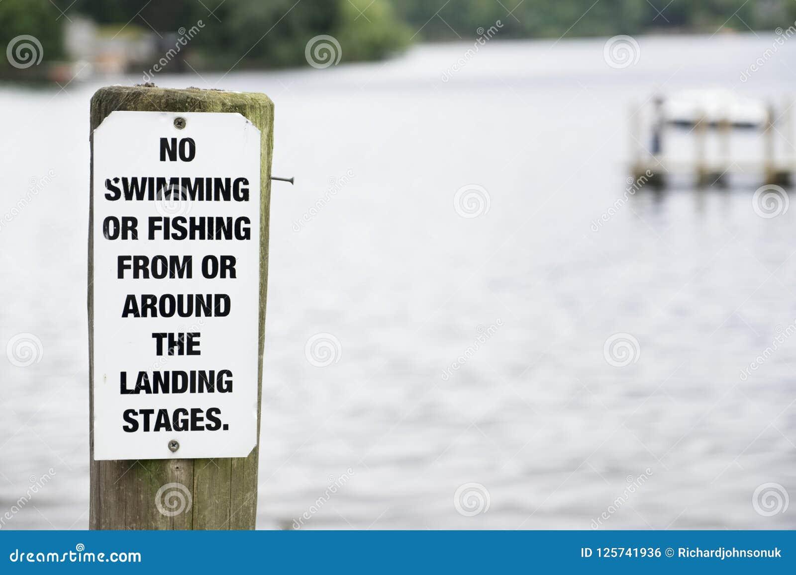 Keine Schwimmen oder Fischen am Seewegweiser auf hölzernem Anlegestellenpier