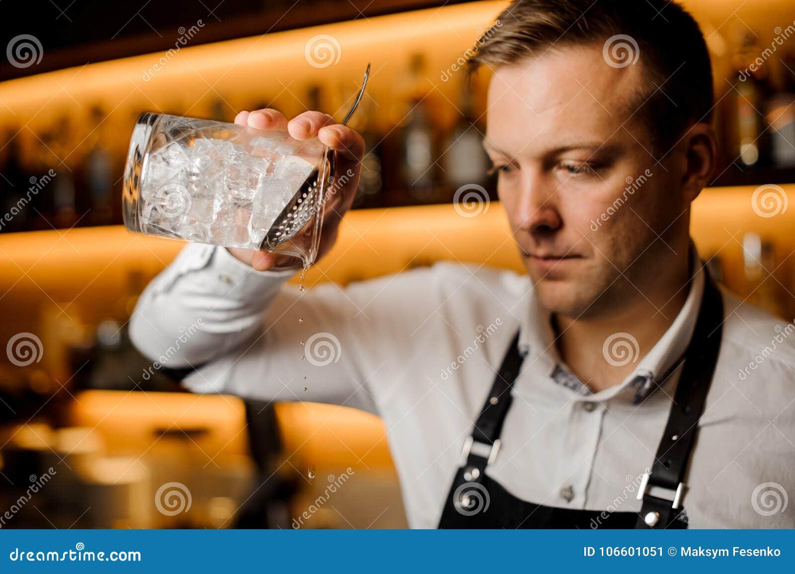 Kellner, der alkoholisches Cocktail mit Eis unter Verwendung des Siebs und des Glases mischt