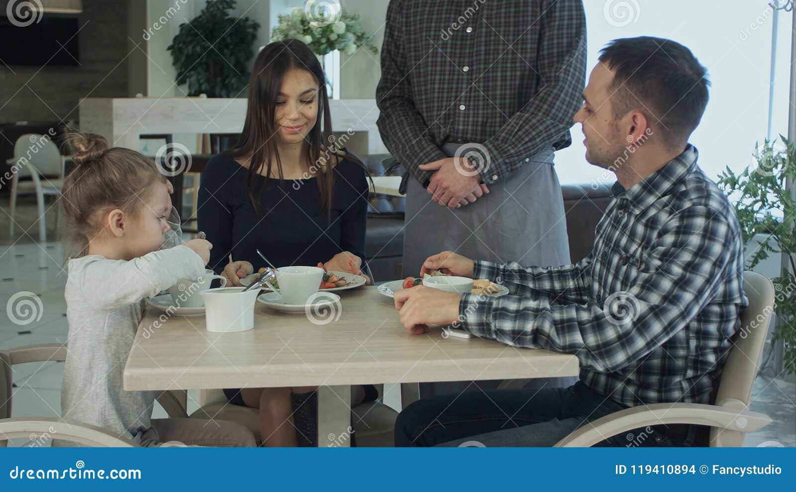 Kellner, der bei Tisch Bestellung der Familie zu Abend isst zusammen entgegennimmt Sie schauend glücklich und erfüllt