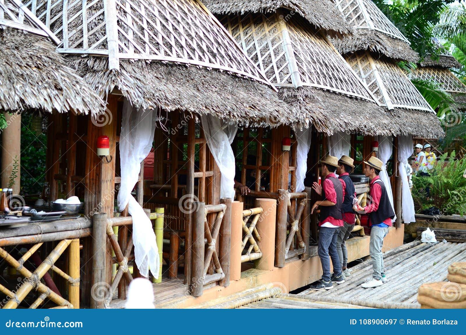 Kellner, die in den Bambus-und Kokosnuss-Blatt-Häuschenhäusern singen