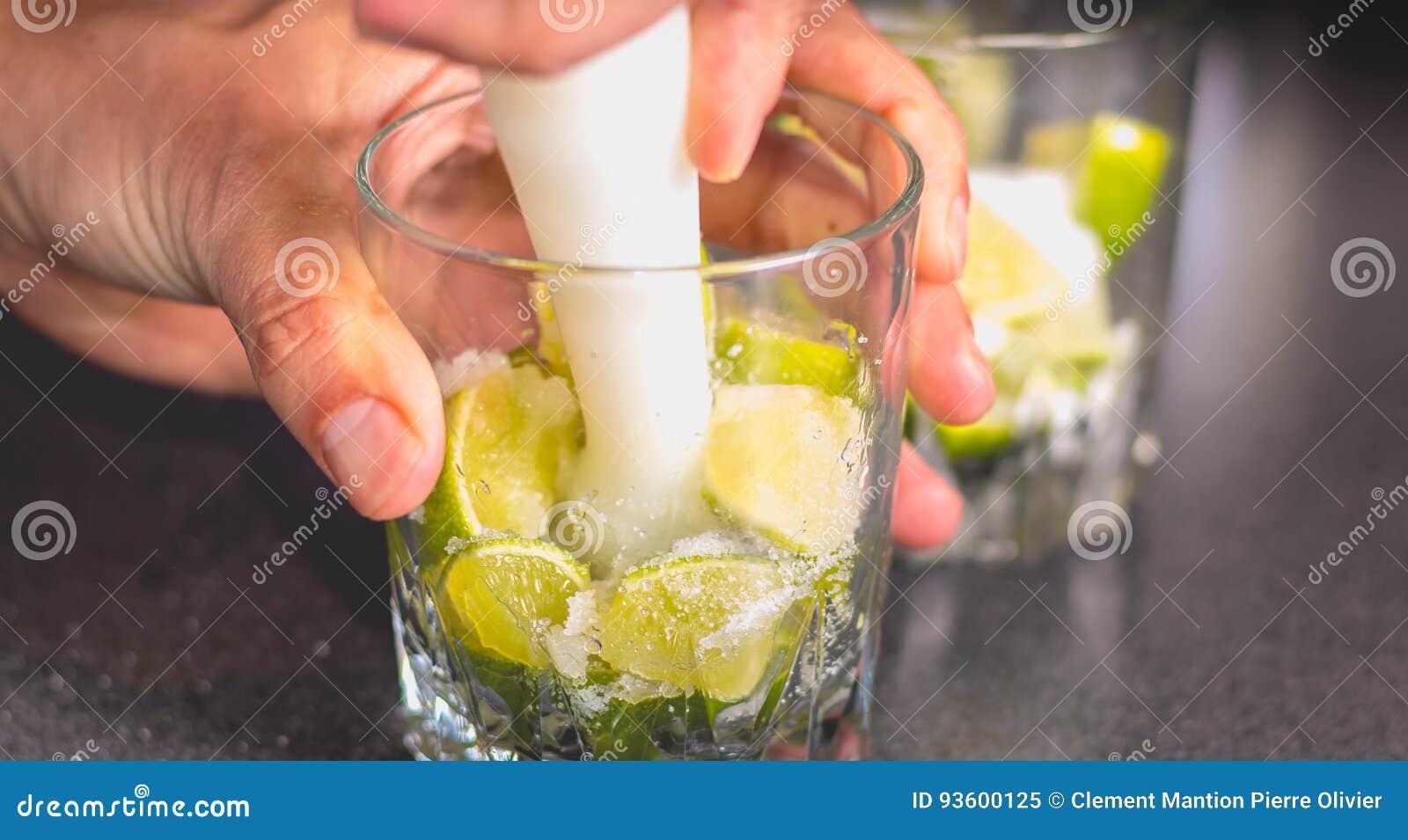 Kellner zerquetscht grüne Zitronen mit einer Pille, um caipirihnas zu machen
