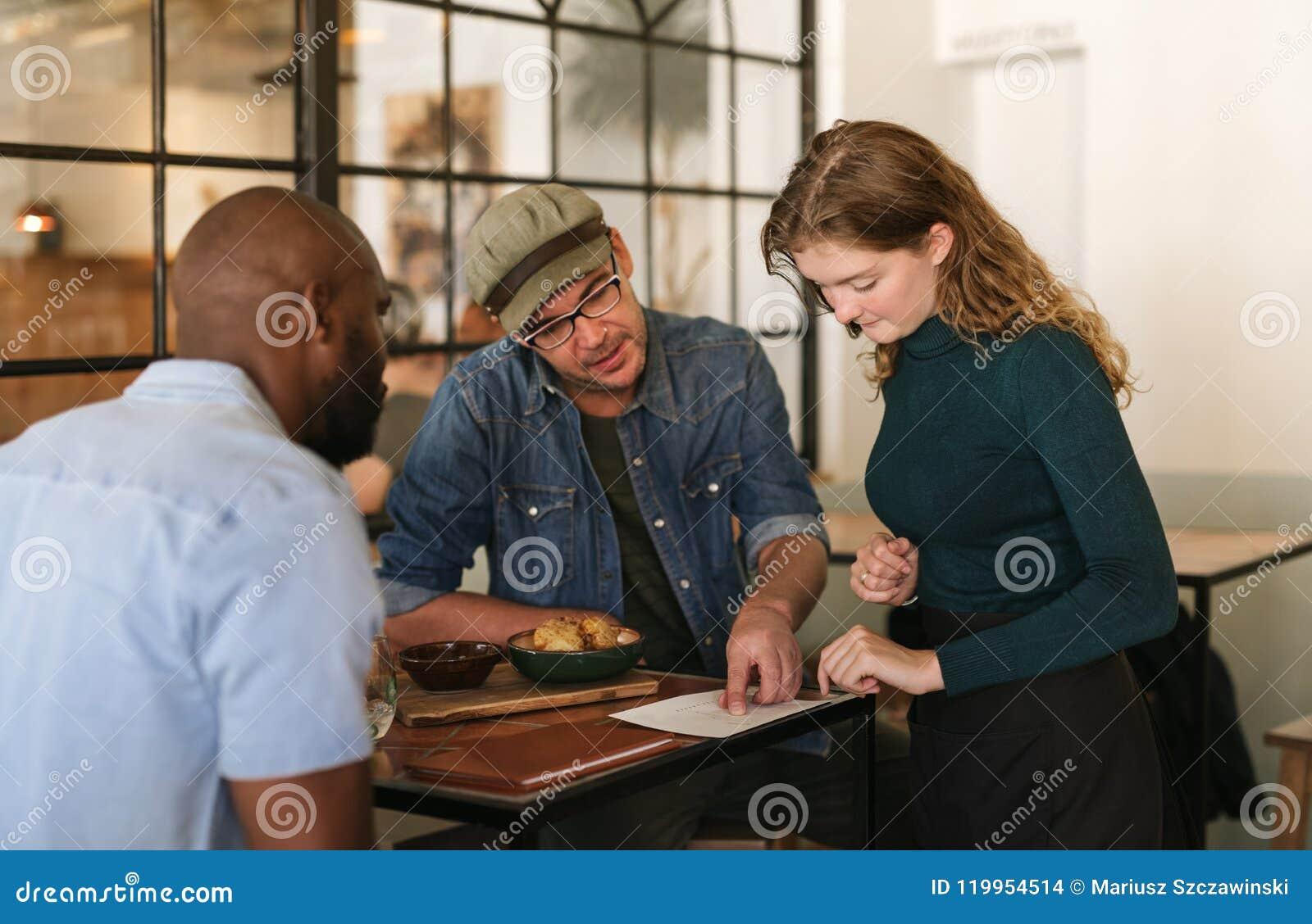 Kellnerin, die das Menü Kunden in einer Bistro erklärt