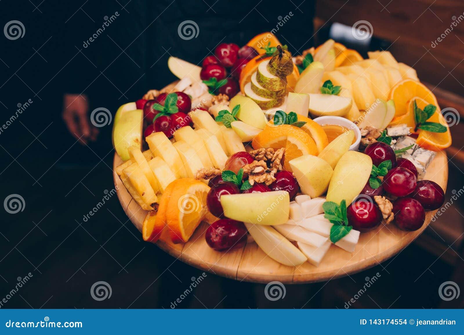 Kelner porcji winogrona, Pomarańczowy Bananowy bonkret Tropikalnych owoc asortyment na białym talerzu przy restauracją dla Alkoho