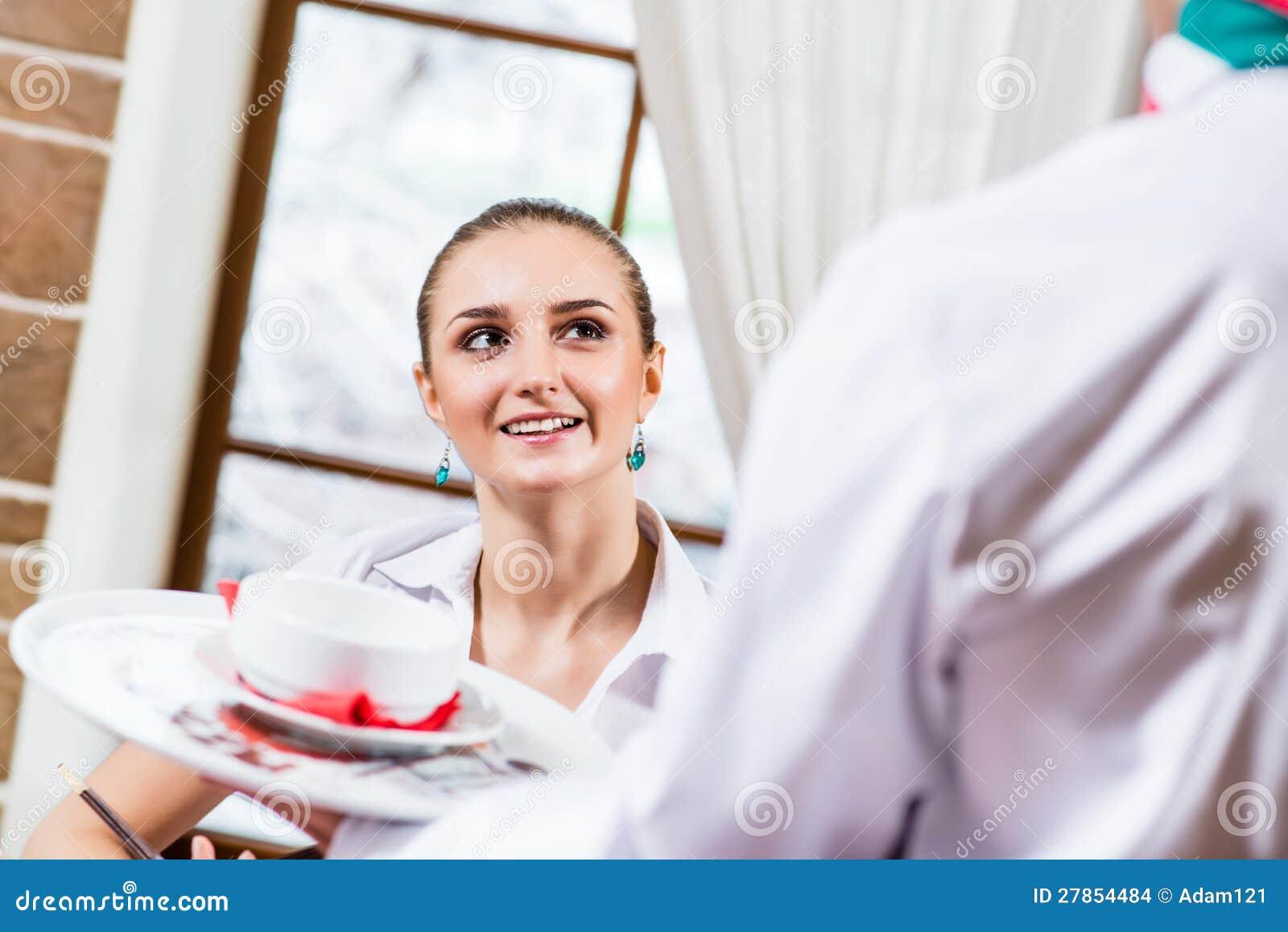 Kelner przynosi naczynie dla ładnej kobiety
