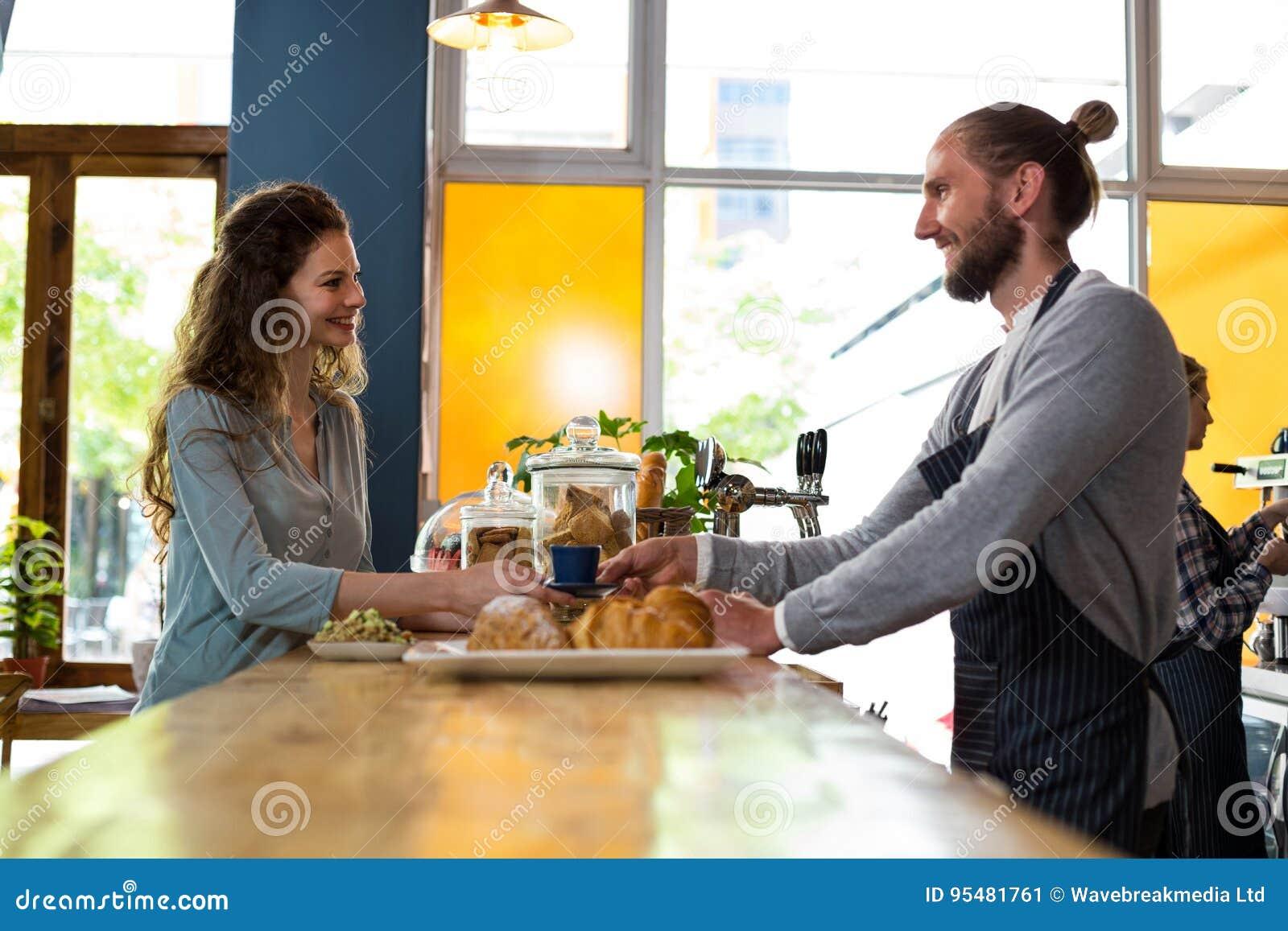 Kelner słuzyć filiżankę kawy klient przy kontuarem