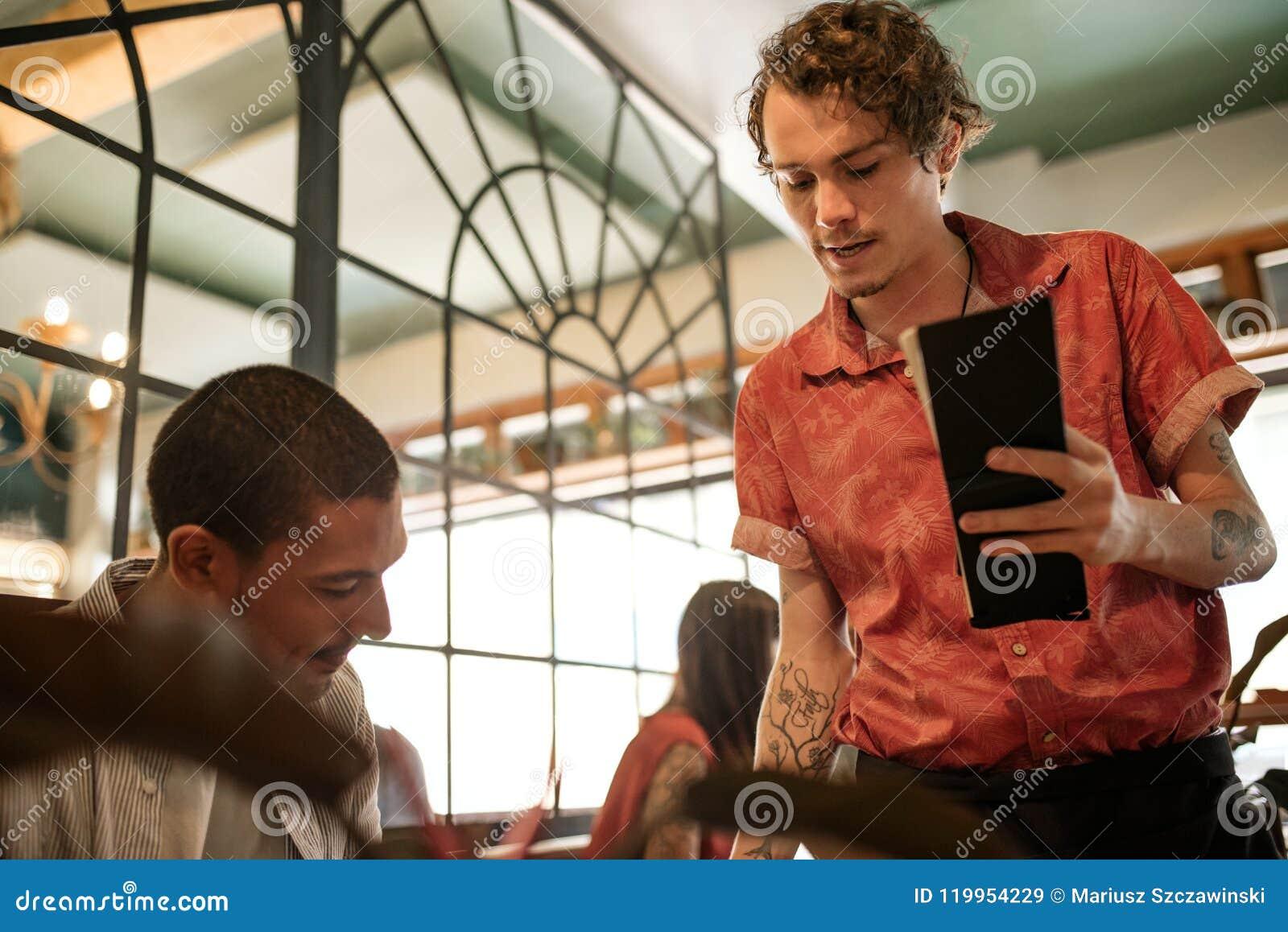 Kelner wyjaśnia menu uśmiechnięty restauracyjny klient