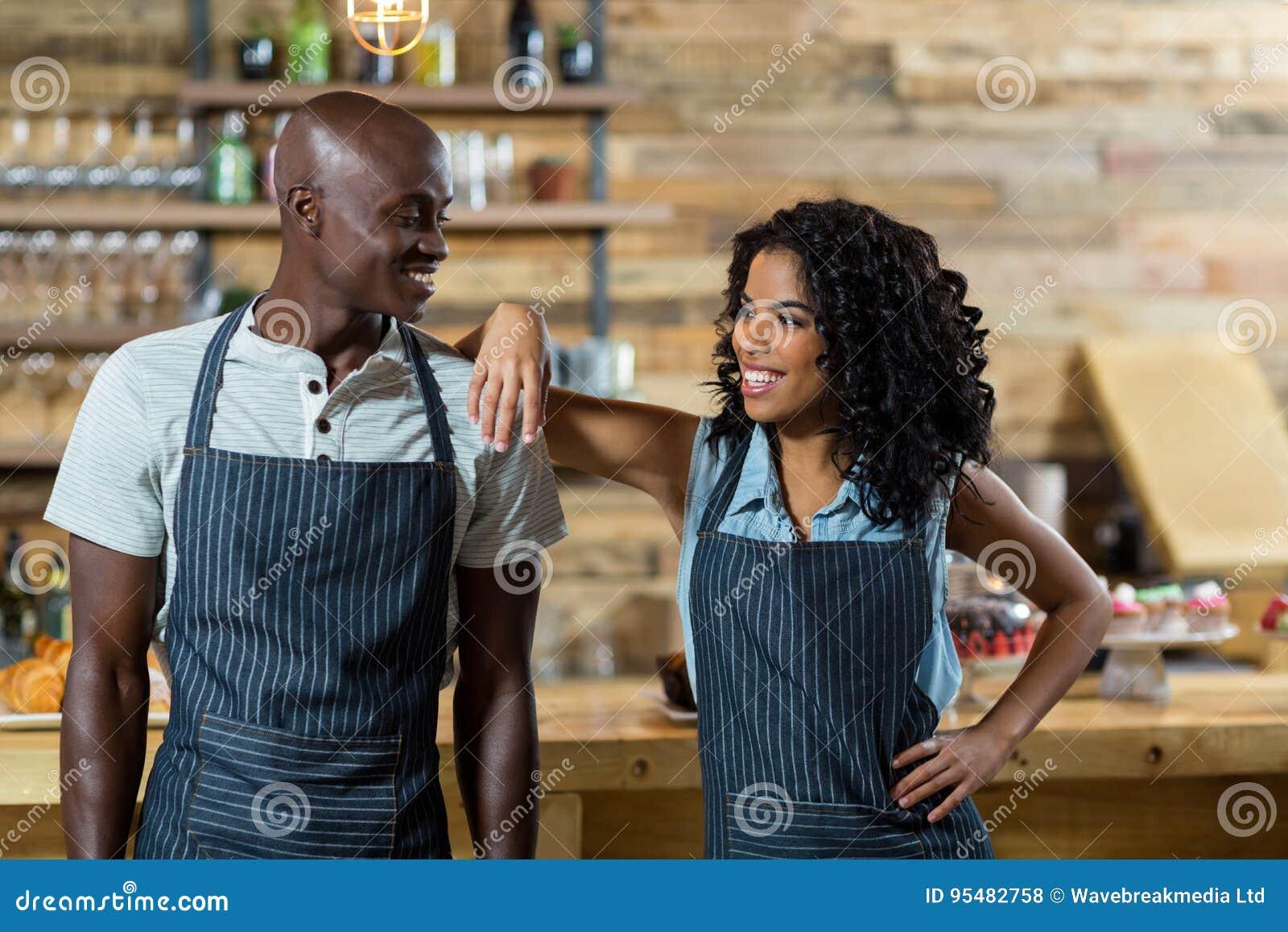 Kelnera i kelnerki pozycja przeciw kontuarowi w café
