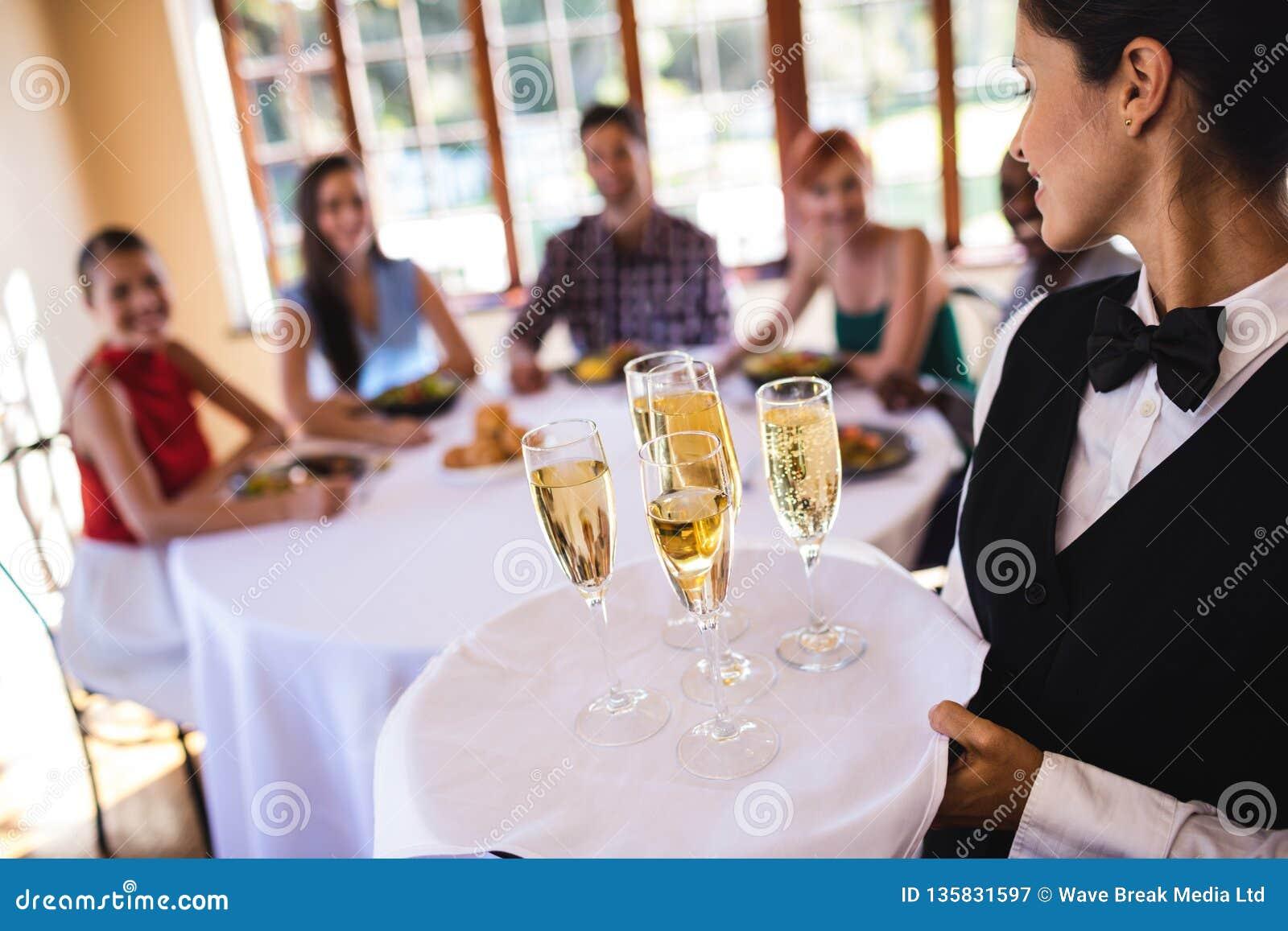 Kelnerek szampańscy szkła na tacy w restauracji