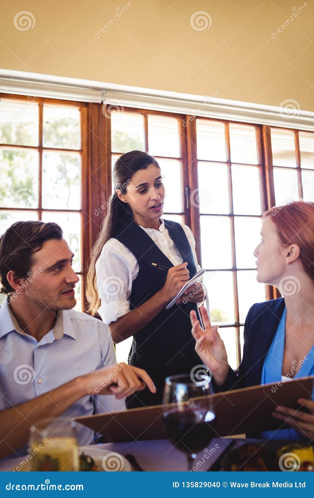 Kelnerka bierze karmowego rozkaz od ludzie biznesu