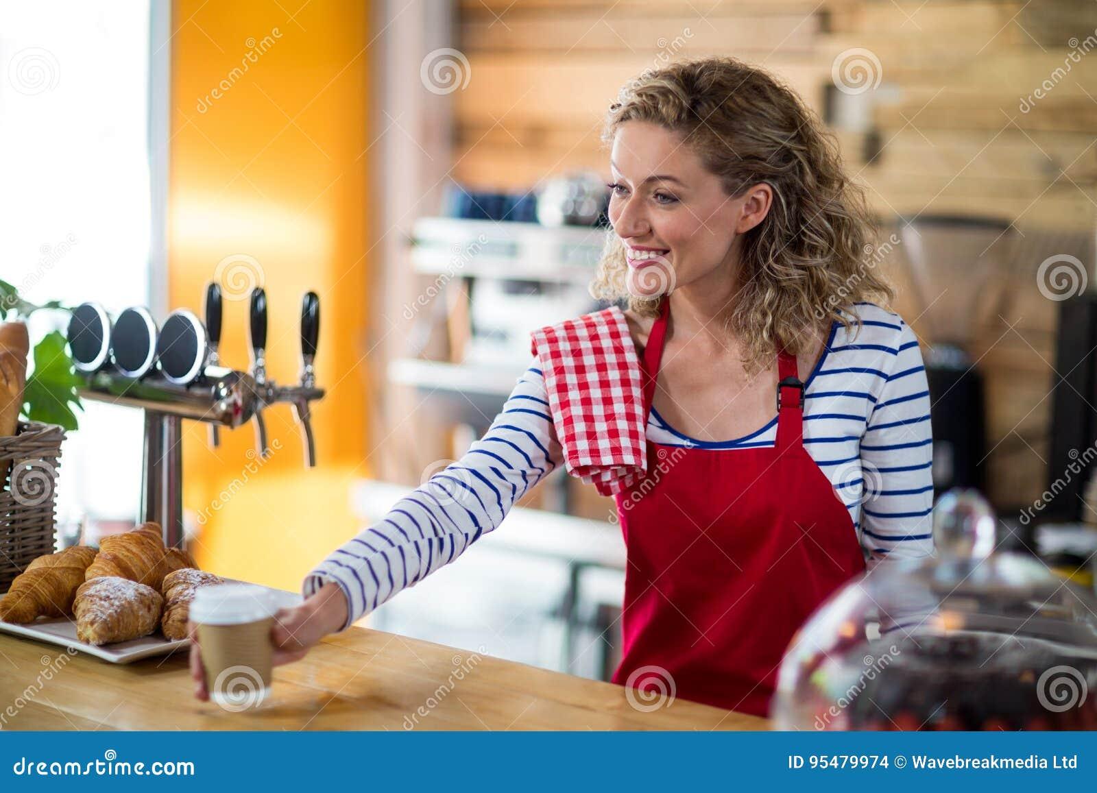 Kelnerka słuzyć filiżankę kawy klient w café