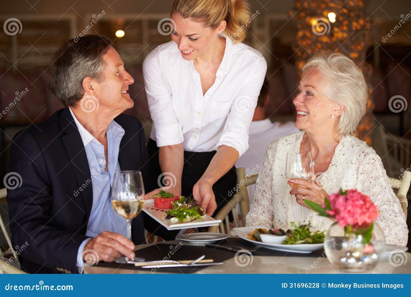 Kelnerki porci jedzenie Starsza para W restauraci
