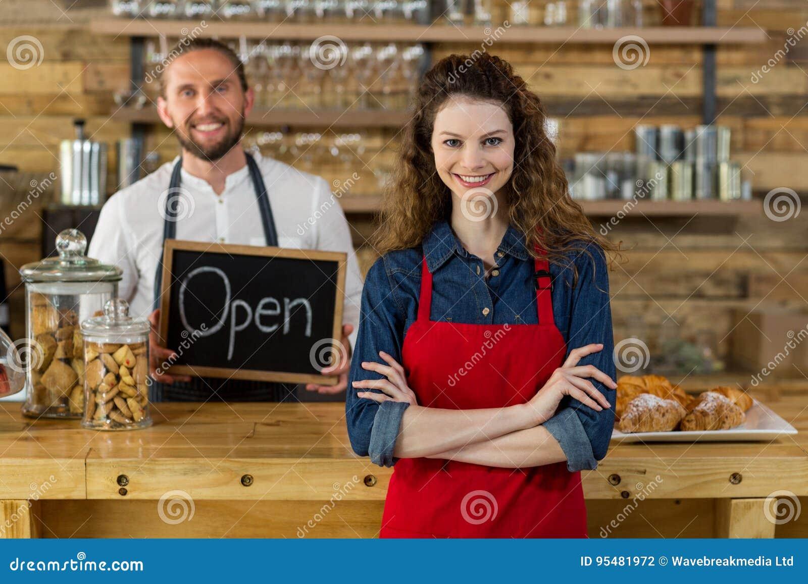 Kelnerki pozycja z rękami krzyżował przy kontuarem w café