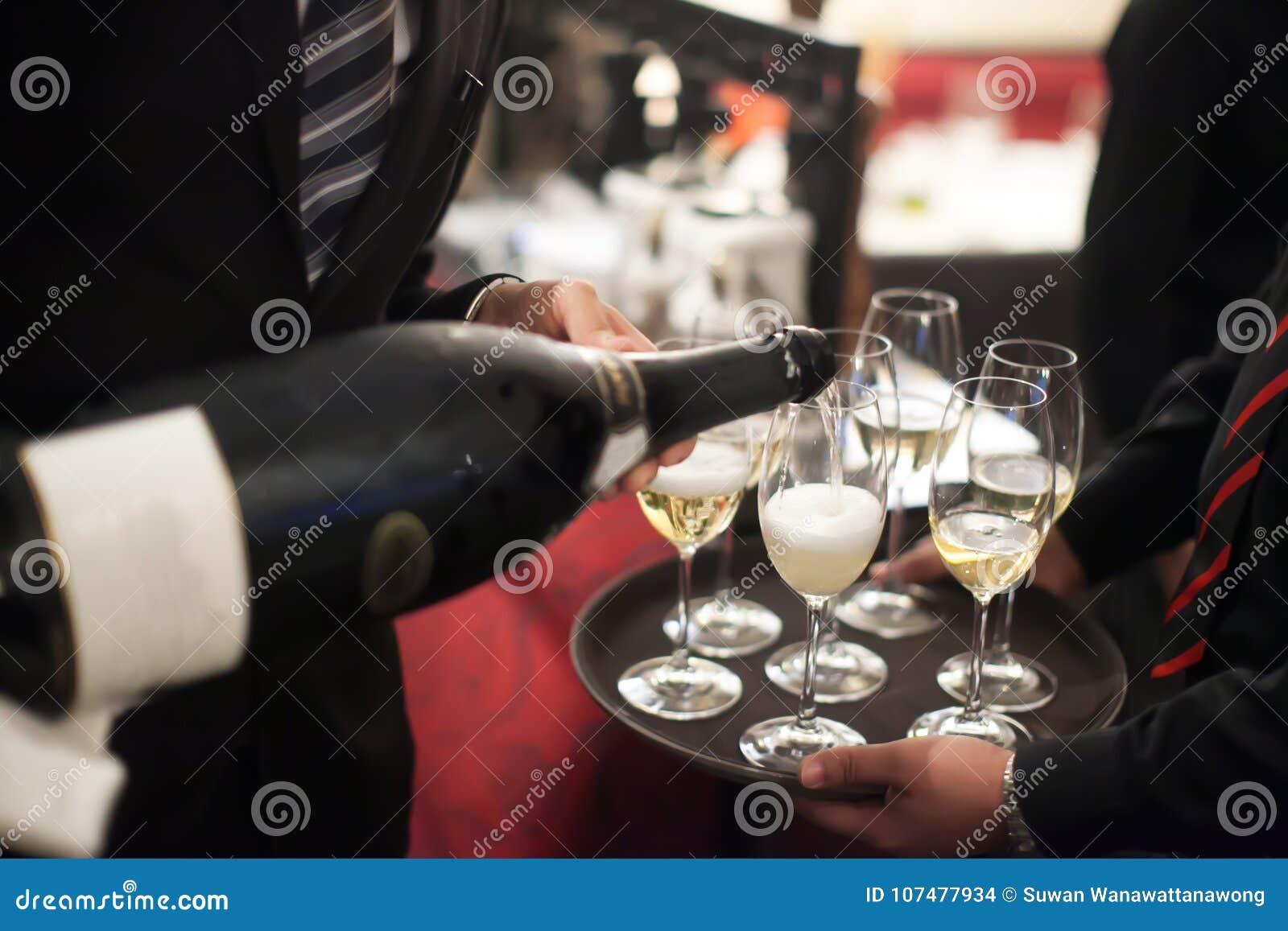 Kelners gietende champagne in het wijnglas in restaurant blur