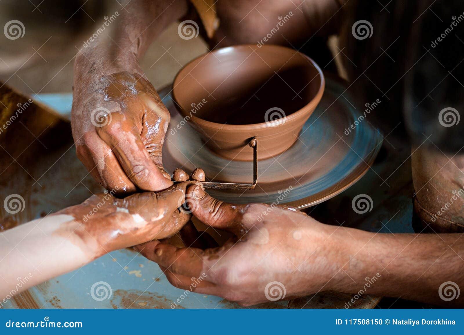 Keramiker` s räcker att vägleda händer för barn` s för att hjälpa honom att arbeta med krukmakerihjulet