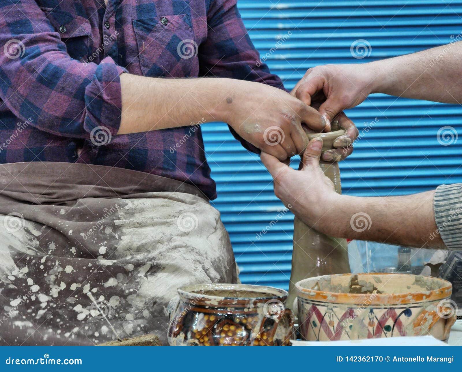 Keramikern undervisar hur man formar leran på hjulet