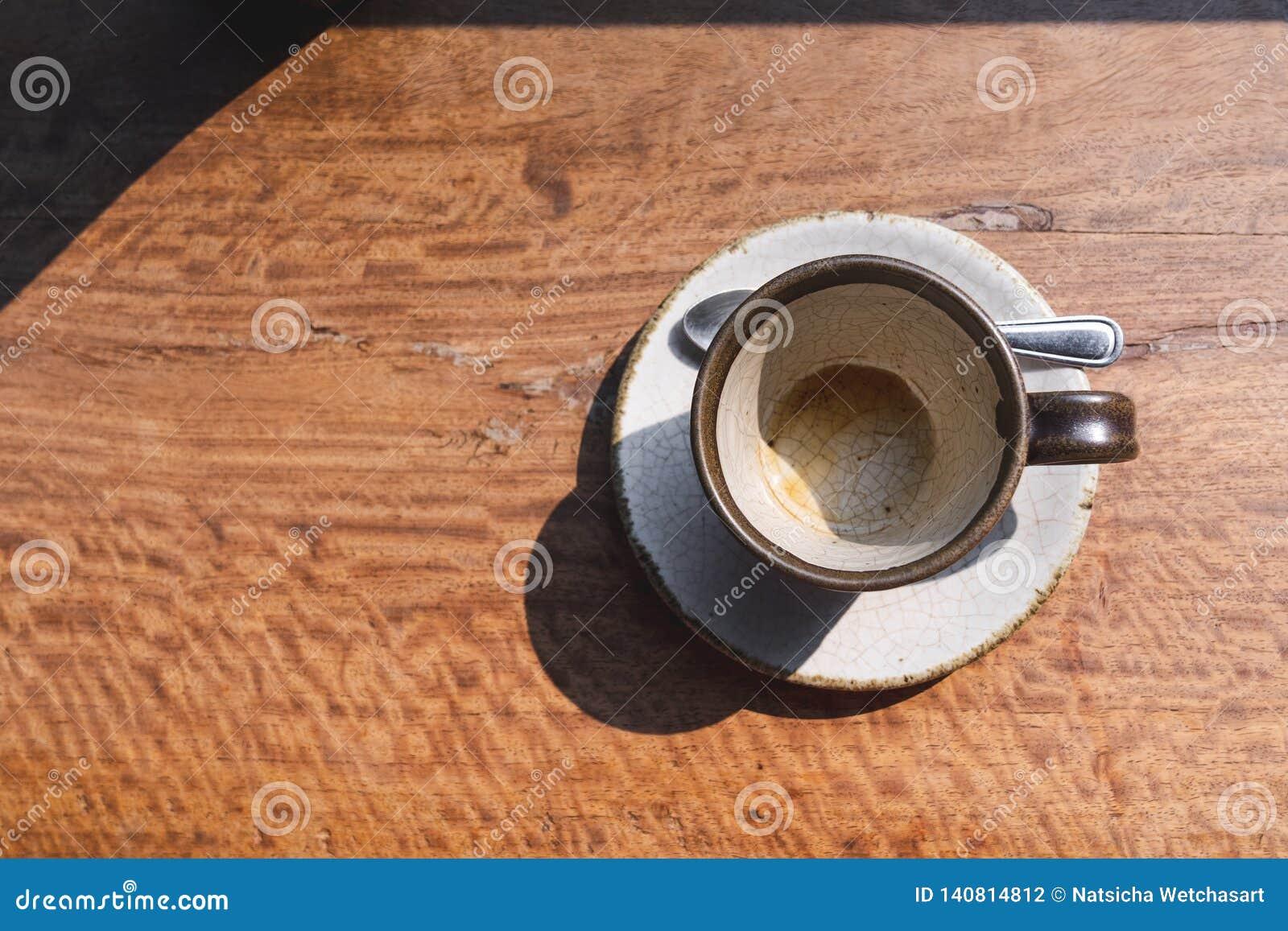 Keramische Schale des leeren Kaffees der Draufsicht auf hölzernem Schreibtisch mit Morgenlicht