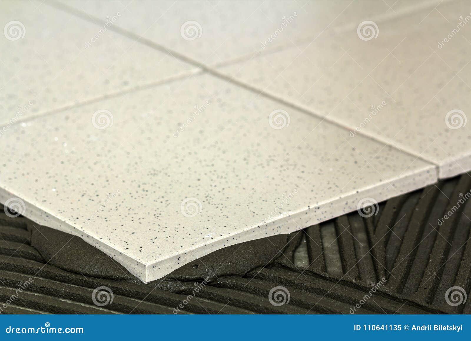 Keramische tegels en hulpmiddelen voor tegelzetter De installatie van vloertegels Hom