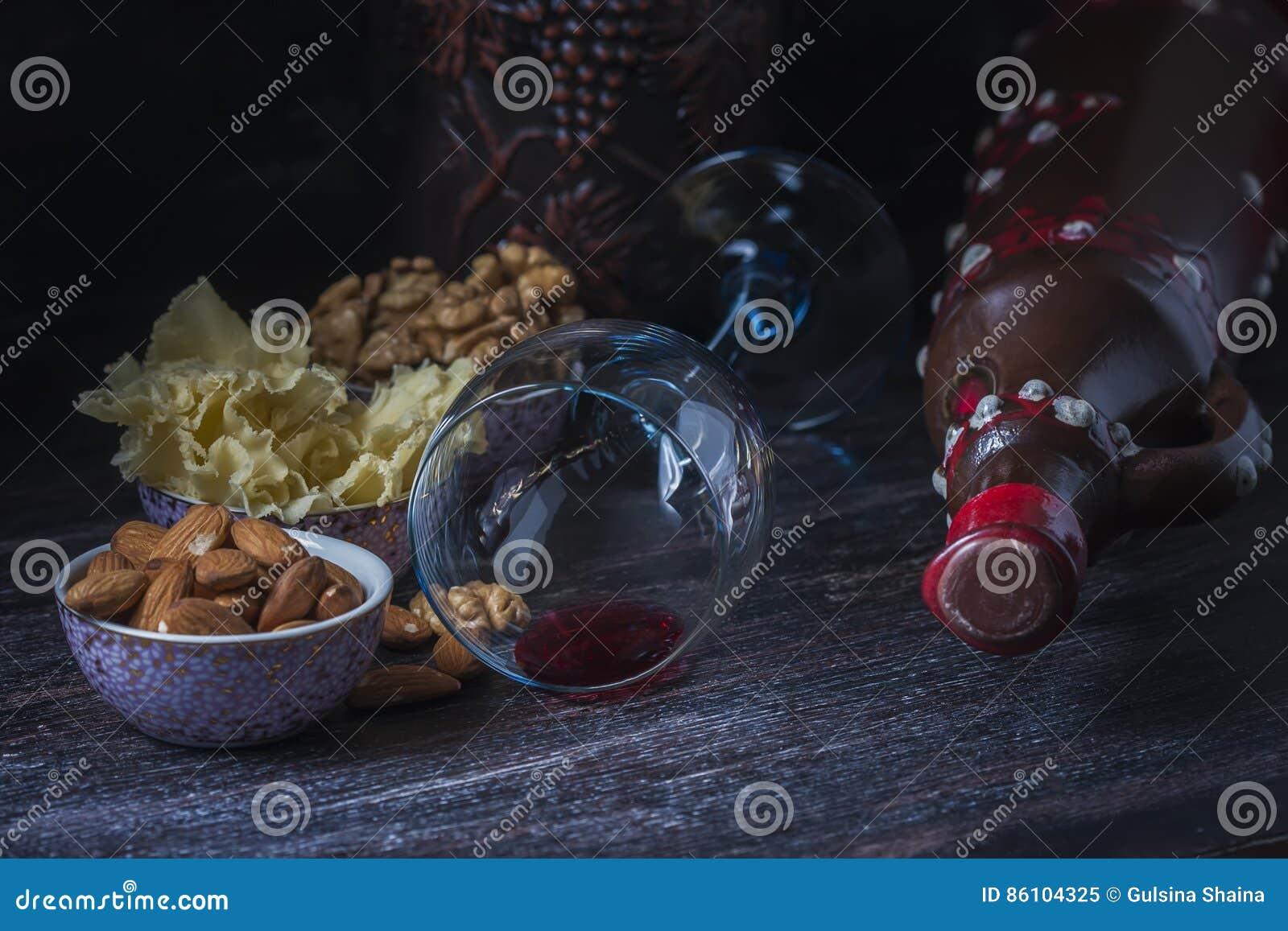 Keramischer Krug für Wein, Käse, Nüsse auf einem hölzernen Brett, Hintergrund