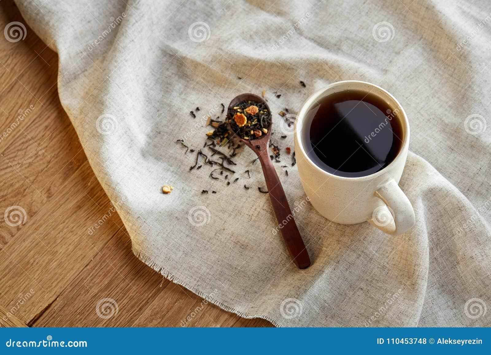 Keramisk kopp te med spridda teblad på en servett på lantlig träbakgrund, selektiv fokus
