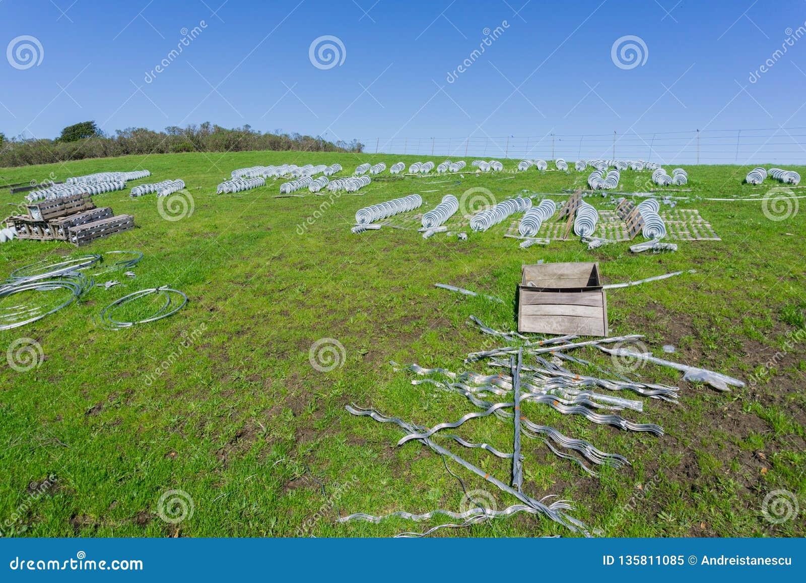 Keramiska isolatorer fördelade på en grön äng som väntar för att byta ut gamla, Kalifornien