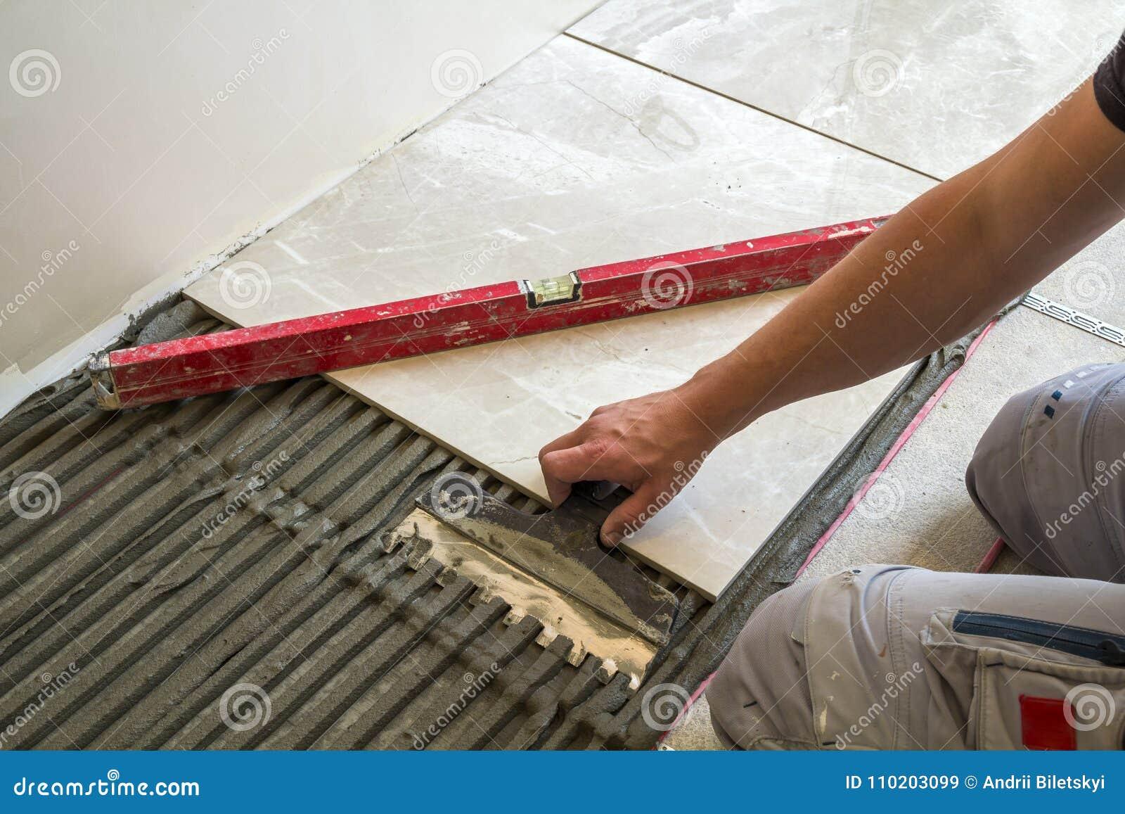 Keramiska tegelplattor och hjälpmedel för tiler Arbetarhand som installerar golvtegelplattor Hemförbättring renovering - bindemed