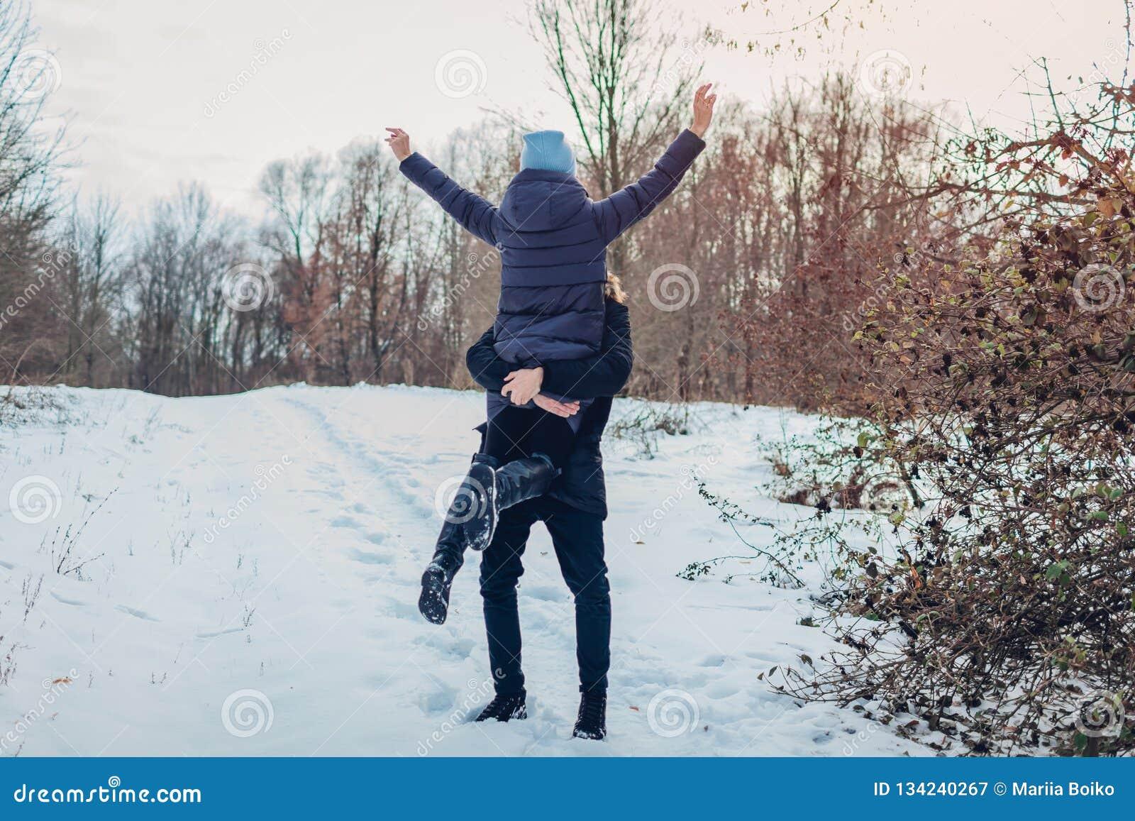 Kerel die en zijn meisje houden de opheffen dient de winter binnen bosmeisje in die wapens opheffen Mensen die pret hebben in ope