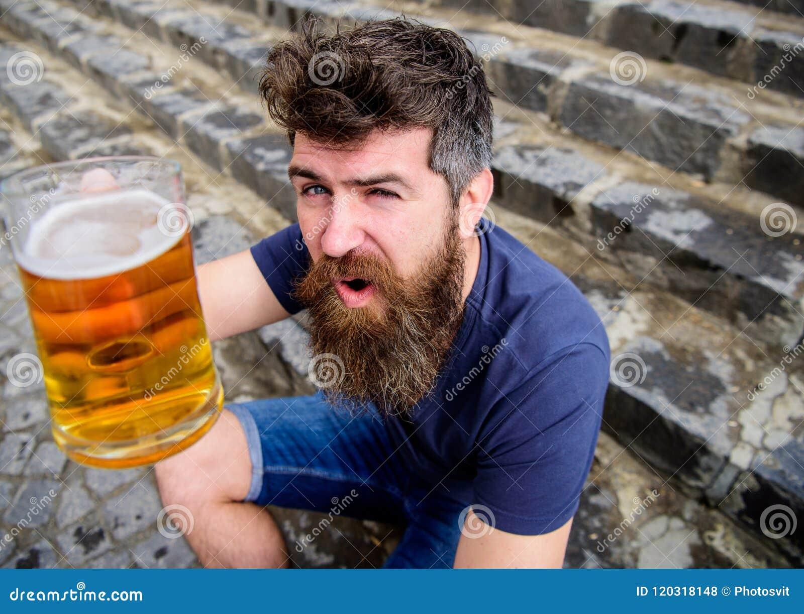 Kerel die rust met koud bier van het vat hebben Hipster op vrolijk gezicht het drinken bier openlucht, omhoog opheffend drank Men