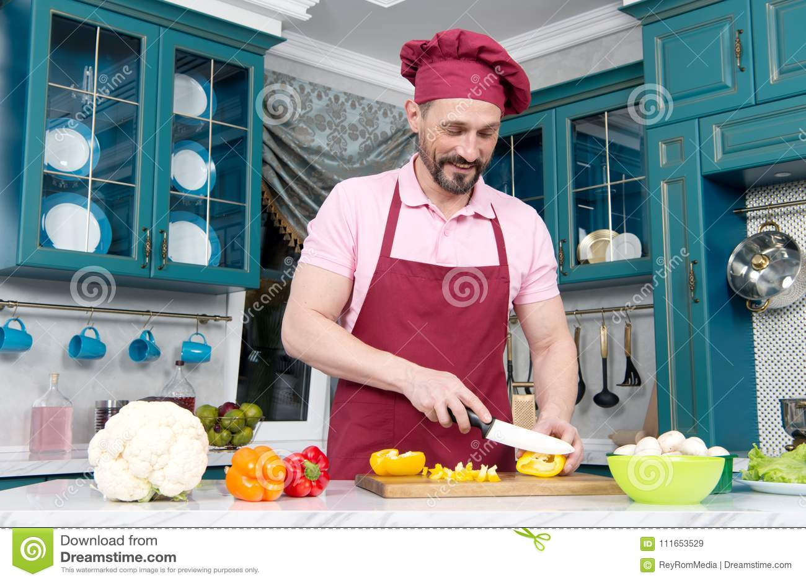 Kerel met messen scherpe oranje peper op lijst De kok gekleed in schort bereidt diner met paprika voor Mens die in hoed groenten