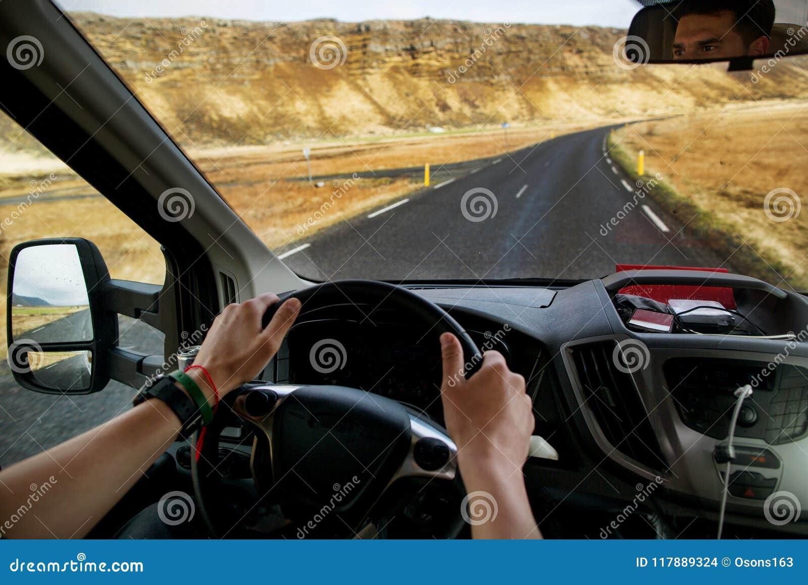 Kereltoerist die een auto in de bergen drijven, die naar IJsland reizen
