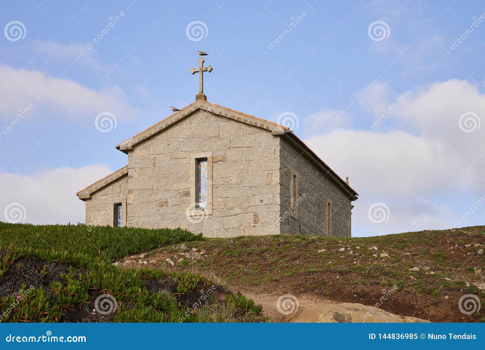 Kerk over de heuvel tegen een blauwe hemel