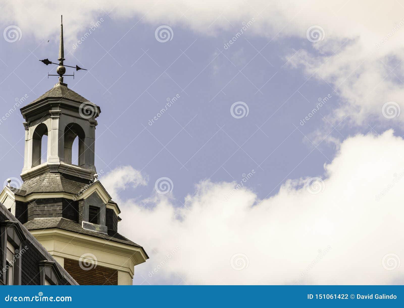 Kerktoren met weathervane en blauwe hemel met wolken