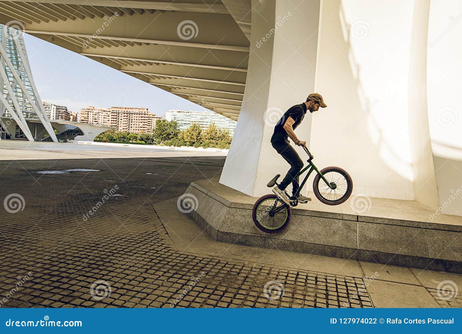 Kerl, der ein bmx Fahrrad auf die Straße reitet Freistil BMX in der Stadt