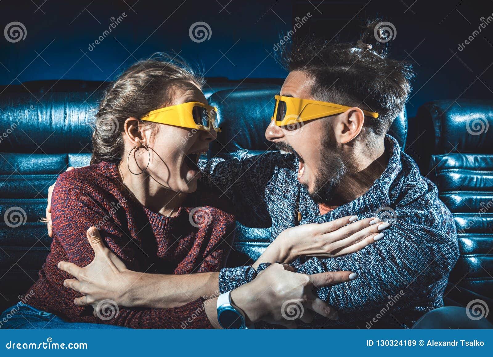 Kerl- und Mädchen3d Gläser sind beim Aufpassen eines Films sehr besorgt