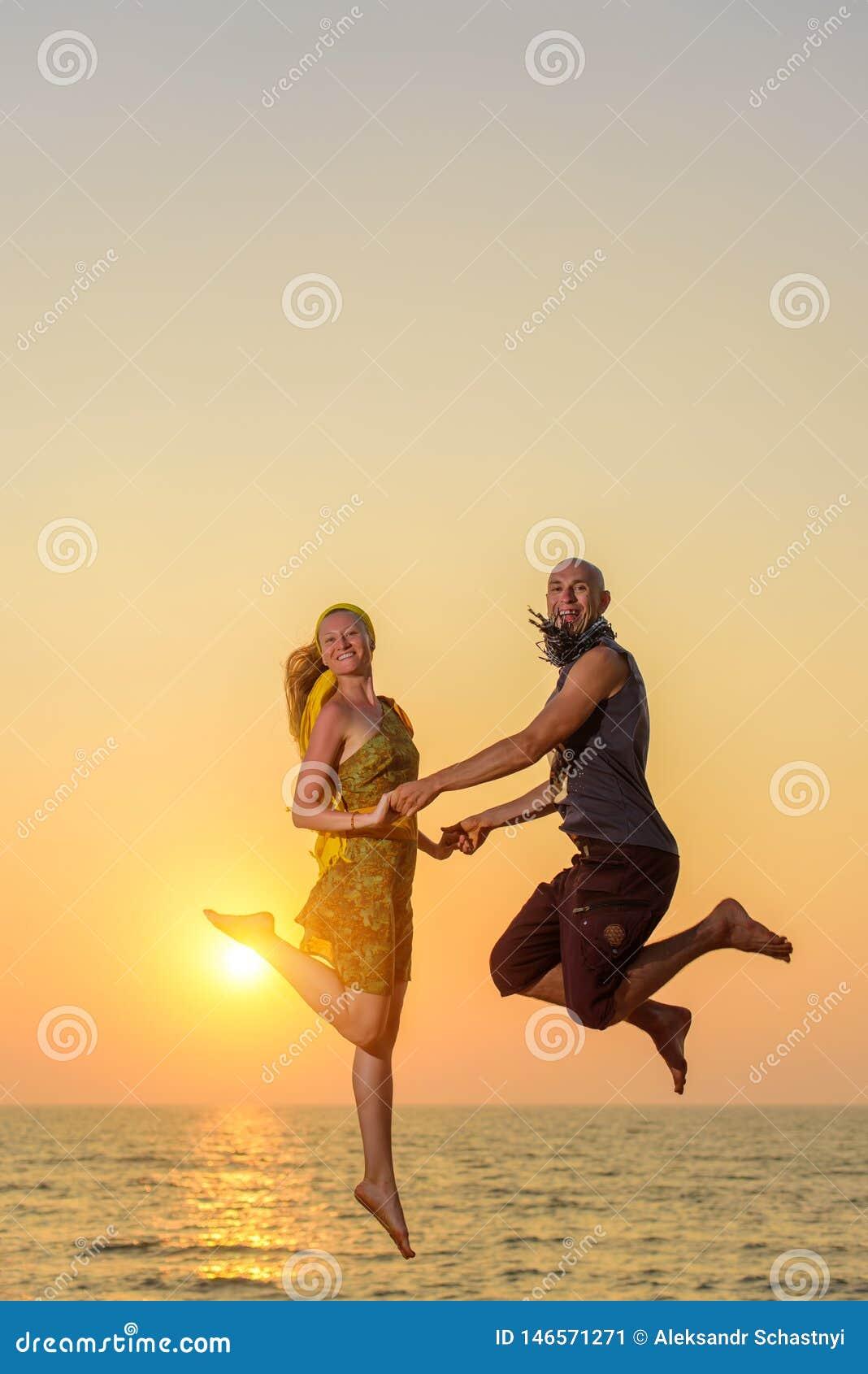 Kerl und Mädchen, die in die Luft auf dem Hintergrund des Meeres springen und Kamera betrachten Junges glückliches Paar springt a