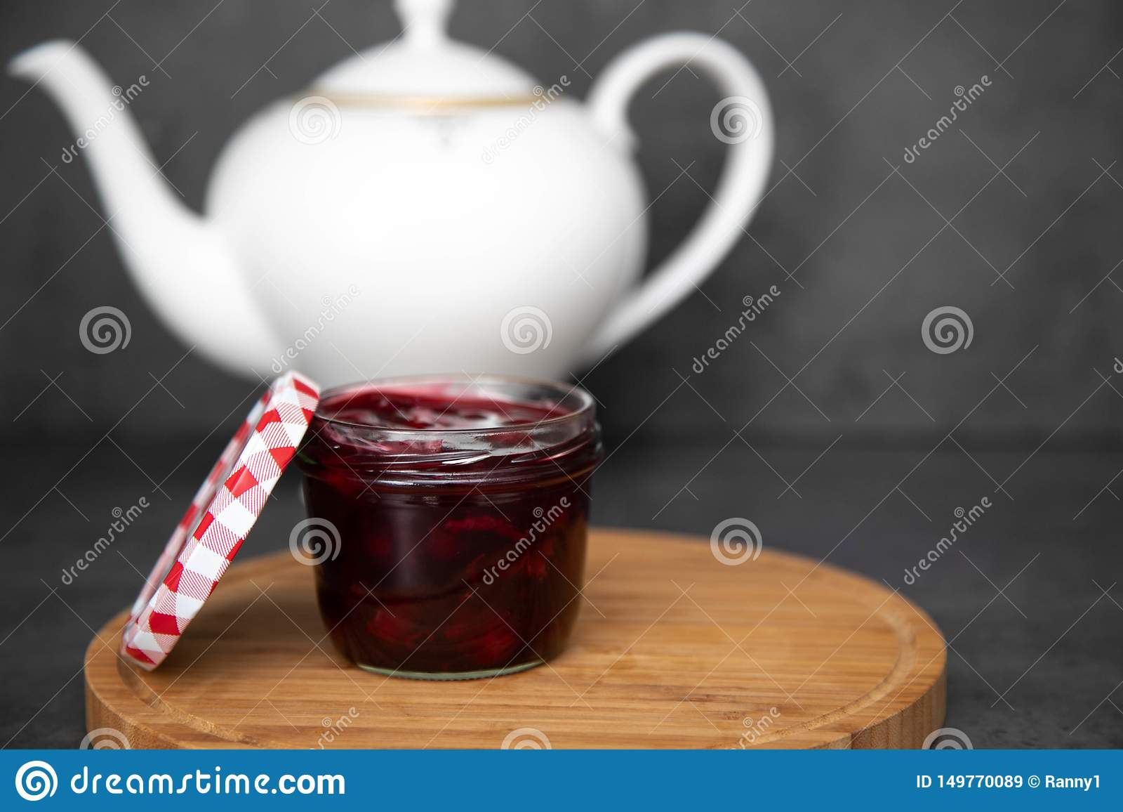 Kersenjam, jam, gelei in een glaskruik met een rood en wit deksel naast een houten ronde raad, raad Tegen de achtergrond van a
