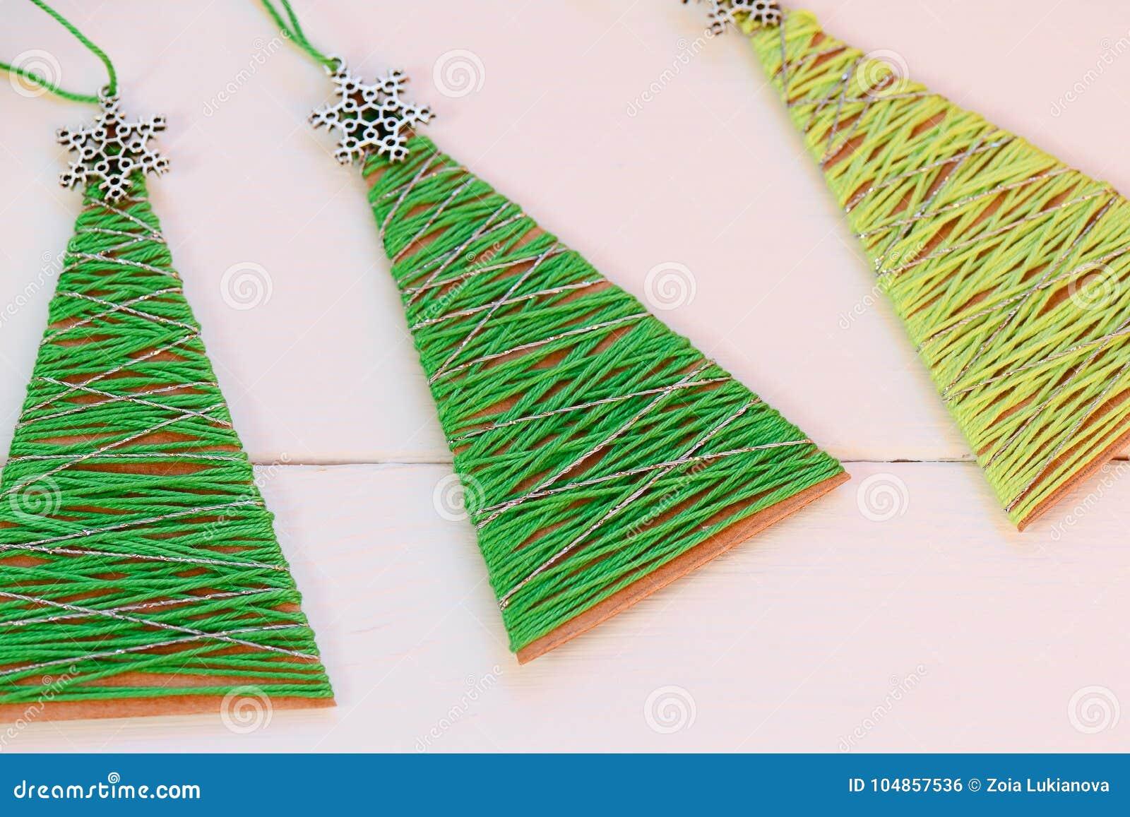 Kerstbomen op een houten lijst Creatieve Kerstbomen die van oud kartondoos en katoenen garen worden gemaakt Gerecycleerde ambacht