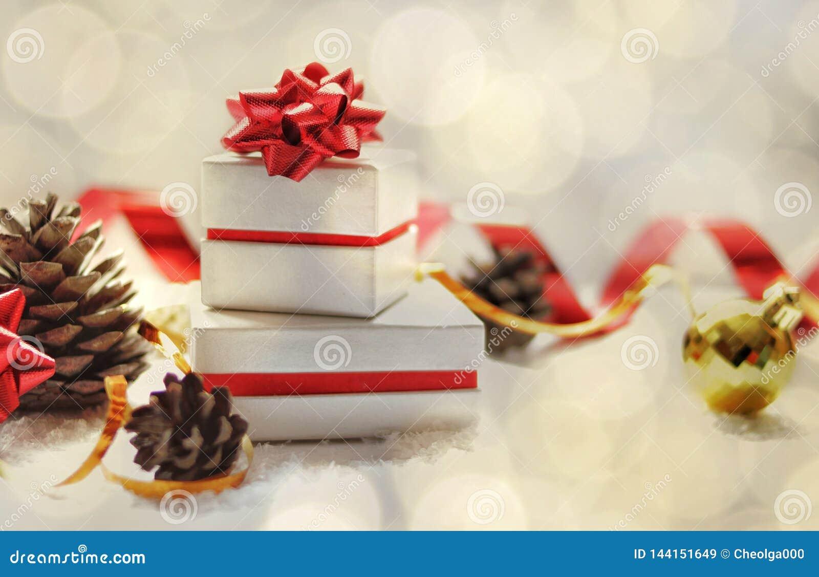 Kerstman Klaus, hemel, vorst, zak De dozen van de Kerstmisgift met een rood buigen, Kerstmisbal, rood lint, kegels op een witte a