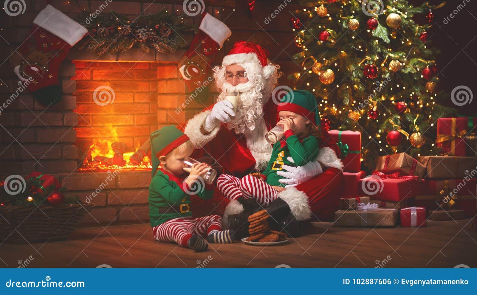 Kerstmis Santa Claus met Elf drinkt Melk en eet Koekjes