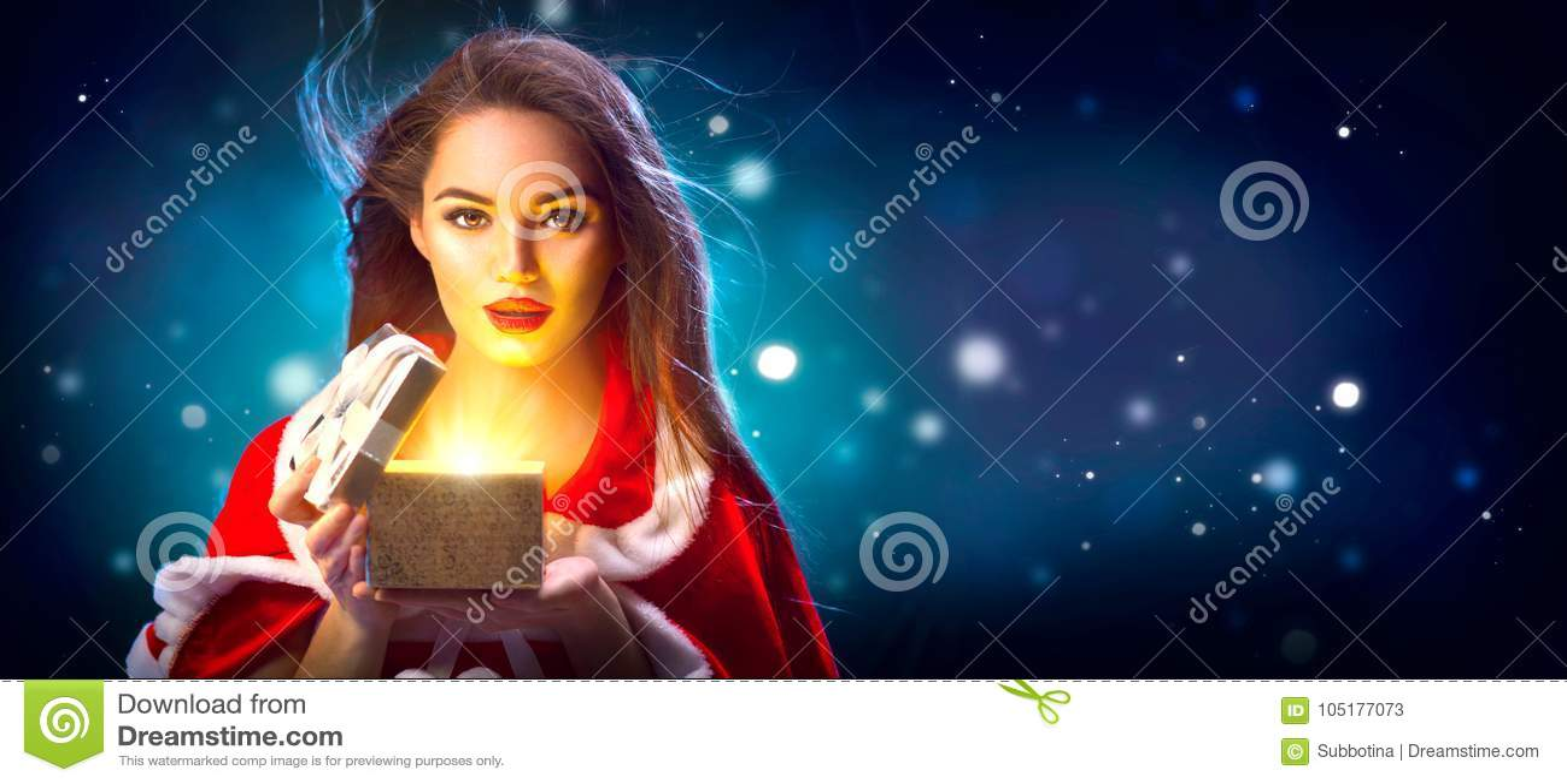 Kerstmis Schoonheids donkerbruine jonge vrouw in partijkostuum het openen giftdoos over de achtergrond van de vakantienacht