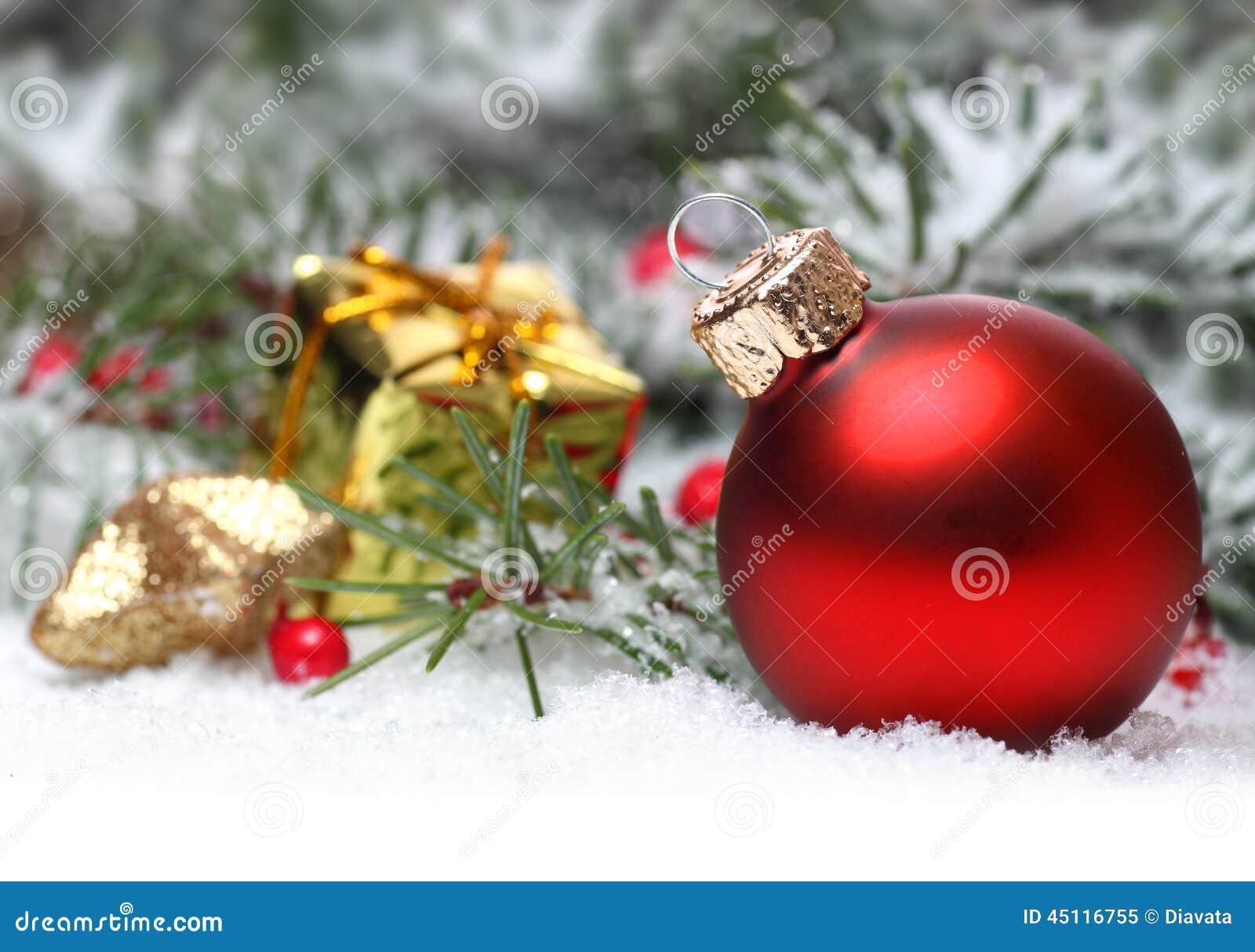 Kerstmisachtergrond met rode snuisterij, bessen en spar in sneeuw