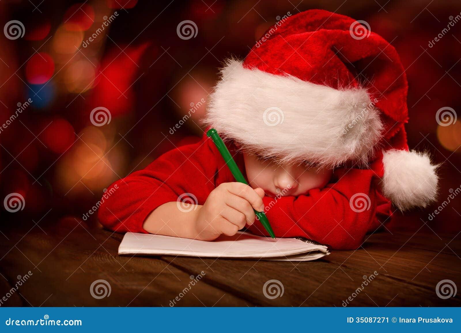 Kerstmiskind het schrijven brief in rode Kerstmanhoed