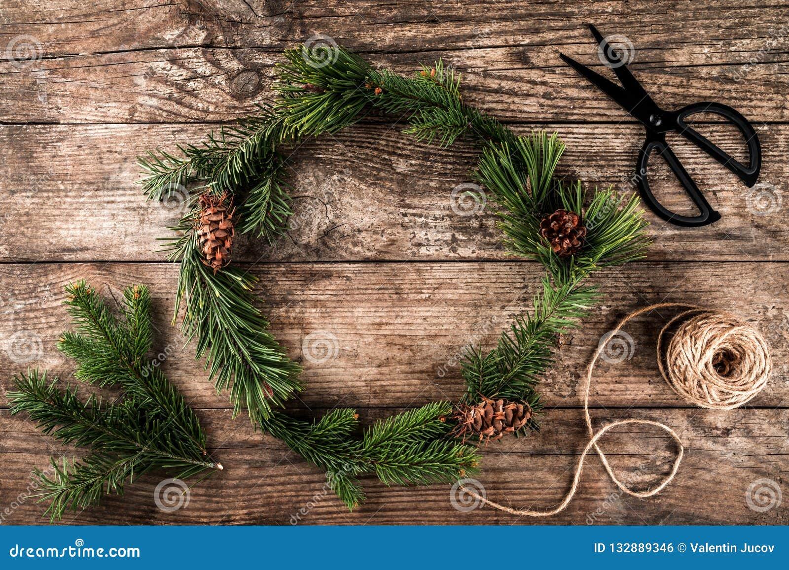 Kerstmiskroon van Spartakken, kegels, schaar en streng van jute op donkere houten achtergrond