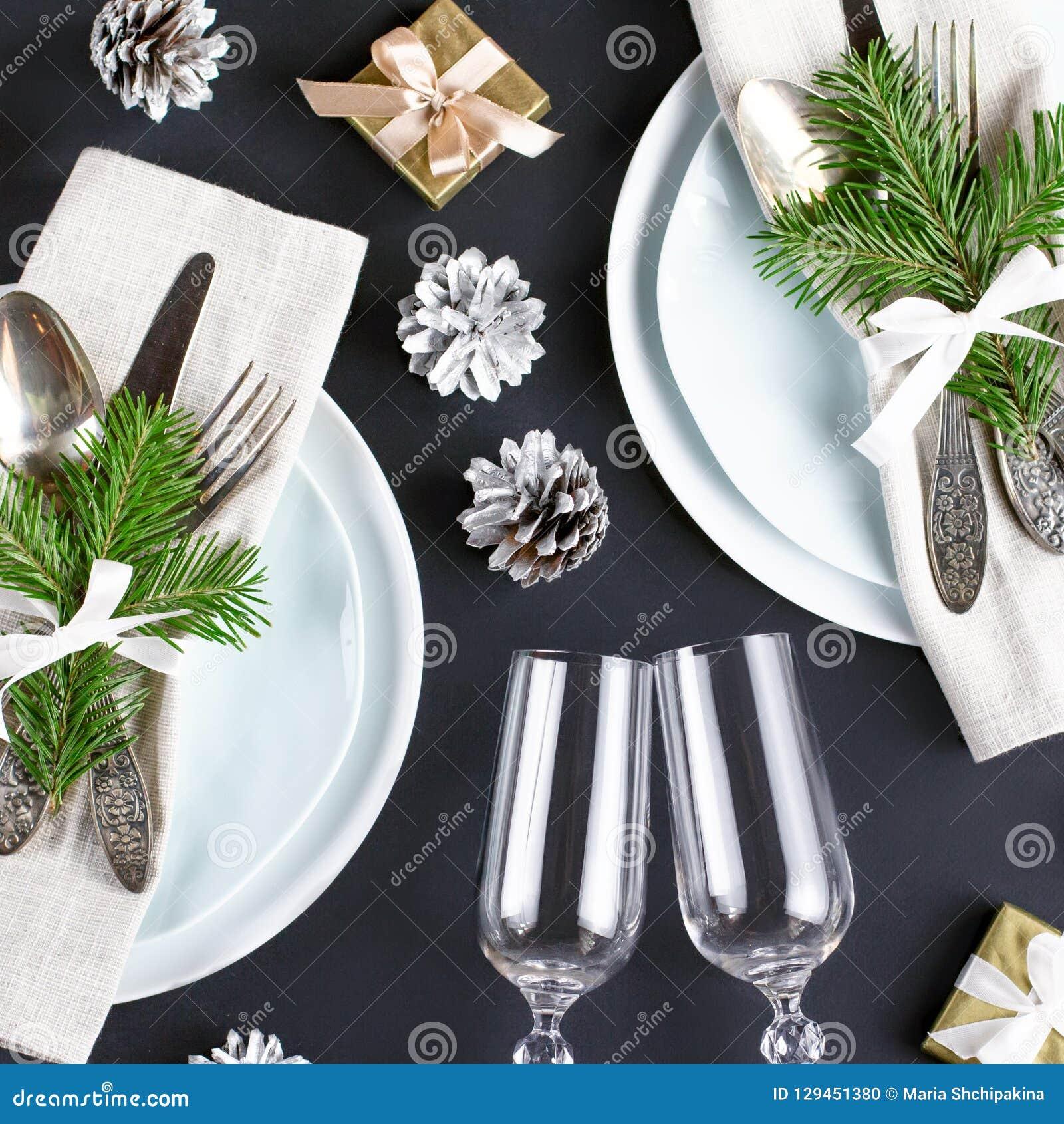 Kerstmislijst die met platen, tafelzilver, giftvakje en decoratie in zwarte en gouden kleuren plaatsen